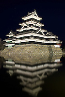 Matsumoto Castle - one of Japan's few original castles - lit up by night, and reflecting in the castle moat.