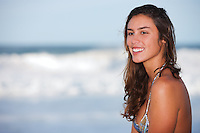 Beautiful very natural looking young brunette looking off camera wearing a bikini.