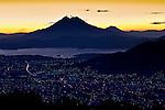 San Vincente Volcano rises above the city lights of San Salvador and Lake Ilopango in El Salvador.