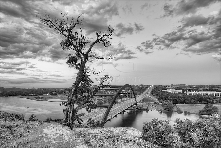 With a full moon overhead and beginning to drop into the Texas Hill Country, Pennybacker Bridge (also known as the 360 Bridge) rests in the early morning hours as clouds drift by. In the distance, the Austin skyline can be seen while the waters of the Colorado River flow by. This black and white Austin image shows an iconic location of the city - one to be enjoyed by anyone willing to walk up the cliff above the bridge.