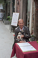 A Chinese man holds his pet dog as he sits outside a  Western-styled restaurant at Tianzifang Art Street in Shanghai, China on November 06, 2009.
