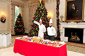 Pastry chefs await the arrival of military children in the State Dining Room of the White House. The theme for the White House Christmas 2011 is Shine, Give, Share - celebrating the countless ways we can lift up those around us, put our best self forward in the spirit of the season, spend time with friends and family, celebrate the joy of giving to others, and share our blessings with all.  The theme translates to the holiday décor on several levels. There is the literal translation through the use of shiny elements – star motifs, quartz and metallics like copper, aluminum and mirrored paper. There is also a conceptual connection – we're inviting visitors to give their thanks to members of our military, and have once again invited guest artists to share their talents working with the White House. This year's décor also includes handmade decorations crafted from simple materials – paper, felt, and even recycled cans. These are projects that anyone can do at home using readily available materials that are inexpensive or free..Credit: Ron Sachs / CNP