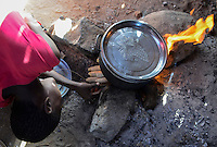 KENYA Turkana, Lodwar,village Kaitese, Turkana tribe, woman cook in kitchen, using remains of corncob as fuel / KENIA, Turkan Dord Kaitese, Herdstelle, Brennstoff Reste von Maiskolben