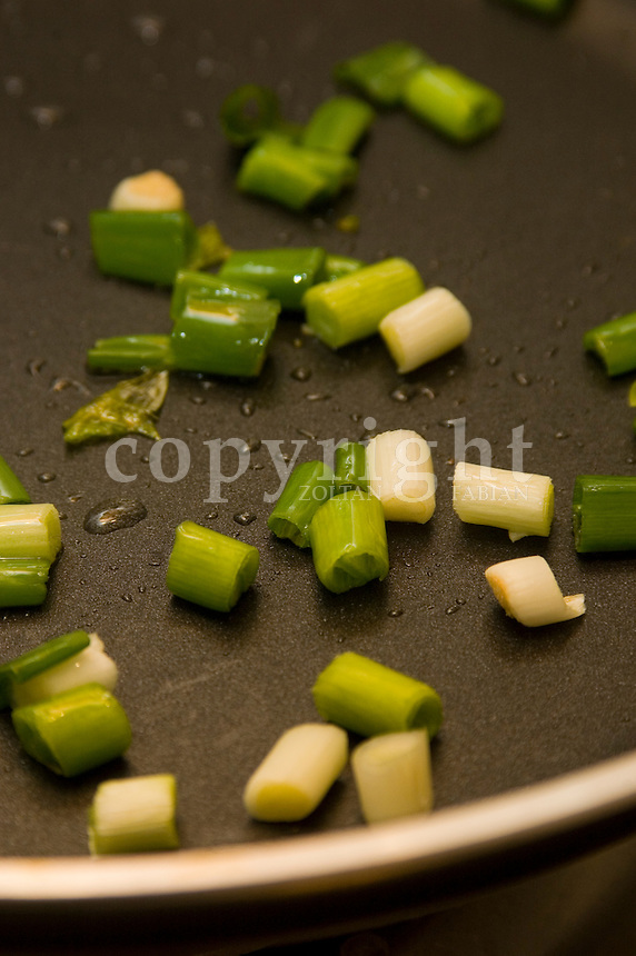Sliced spring onions in a frying pan