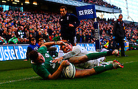 01.03.2015.  Dublin, Ireland. 6 Nations International Rubgy Championship. Ireland versus England. Robbie Henshaw (Ireland) grounds the ball to score a try despite the close attention of Alex Goode (England).