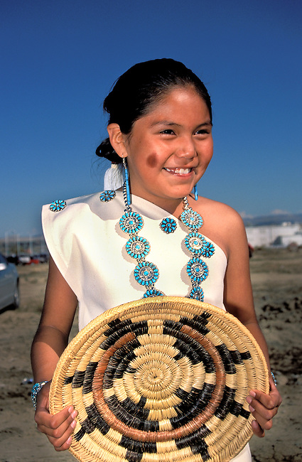 A young participant of the Naatsiilio (Rainbow) Dancers is dressed in a traditional Navajo cotton dress adorned with turquoise and holds a traditional basket