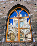 Siena, Tuscany, Italy<br /> Facade of Siena's Duomo, an 11th century Gothic style cathedral reflected in a window on the Piazza del Duomo