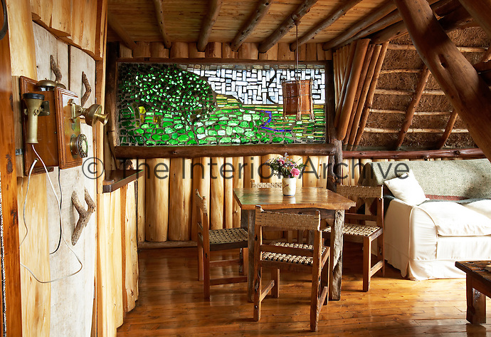 The living room of a boutique style luxurious wooden treehouse, made entirely of wood and grass. The interior has a rustic feel, with the talents of regional artists adding many of the finishing touches. Wooden table and chairs provide an informal eating area.