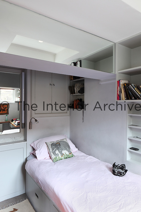A guest bedroom in an apartment with a single bed and built in storage, which makes the best use of the small space
