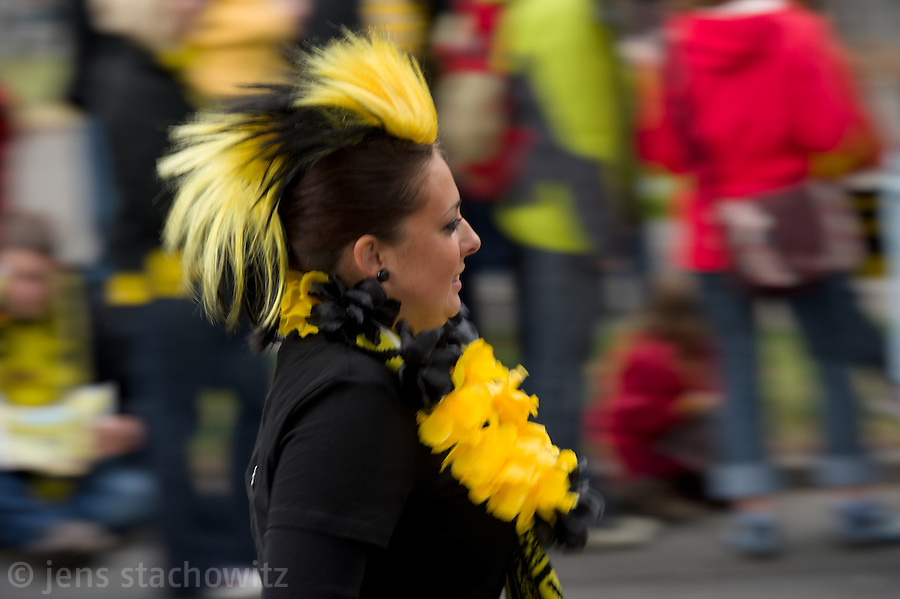 A young woman presents her Mohawk haircut with the club colors yellow and black during the victory parade. - In Dortmund fans celebrated a gigantic party because of the title win of their favorite soccer club BVB 09 in the German Premium League.