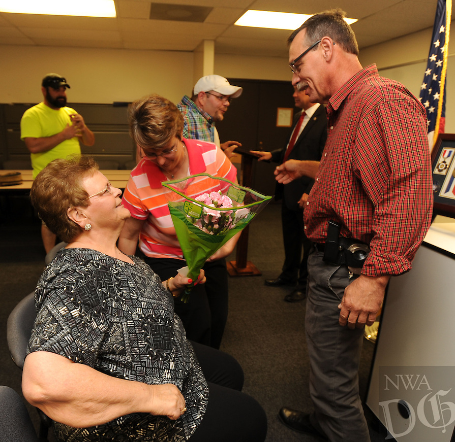 NWA Democrat-Gazette/ANDY SHUPE<br /> John Schuster (right), a detective with the Washington County Sheriff's Office, speaks with Myrrah Mueller (left) of Farmington, and her children Paula Mueller (center) and John Mueller both of Prairie Grove, Wednesday, Sept. 2, 2015, during a ceremony to award the Muellers with the American Police Hall of Fame Medal of Honor at the University of Arkansas Police Department in Fayetteville. Myrrah Mueller's husband, West Fork Police Chief Paul Mueller, was shot and killed on March 20, 1981, while making a traffic stop in West Fork following a robbery in Fayetteville. Schuster, then an officer with the Fayetteville Police Department, was shot twice as he exchanged gunfire with the suspects four days later.