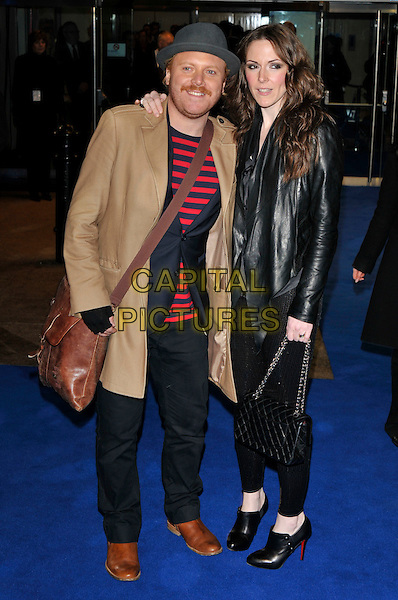 "LEIGH FRANCIS & GUEST .Arrivals - World Premiere of ""Avatar"",  Odeon Leicester Square, London, England, UK, December 10th, 2009..full length couple Avid merrion beige camel coat red striped jumper blue navy t-shirt trousers brown shoes cross body bag black leather jacket grey gray hat chanel ankle booties shooboots boots Christian Louboutin .CAP/PL.©Phil Loftus/Capital Pictures."