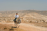 Chemi, a settler, rides his donkey in the unauthorized Israeli outpost of Bnei Adam, West Bank.