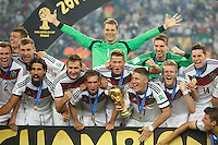 Philipp Lahm and Bastian Schweinsteiger of Germany lift the World Cup trophy after winning the 2014 final celebrating with team mates