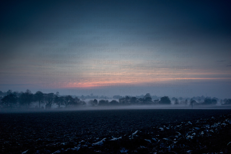 Mist lying low over fields in Suffolk countryside