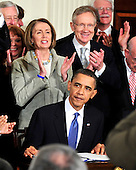 Washington, D.C. - March 23, 2010 -- United States House Speaker Nancy Pelosi (Democrat of California) and U.S. Senate Majority Leader Harry Reid (Democrat of Nevada) applaud as U.S. President Barack Obama signs the version of the health care bill that was passed by the U.S. House of Representatives in the East Room of the White House in Washington, D.C. on Tuesday, March 23, 2010. .Credit: Ron Sachs / CNP.(RESTRICTION: NO New York or New Jersey Newspapers or newspapers within a 75 mile radius of New York City)