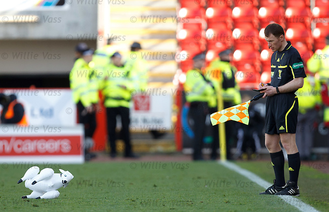 Linesman Stuart Stevenson takes down the particulars of a sheepish pitch invader