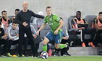 LOS ANGELES, CA - OCTOBER 29: Brad Smith #11 of Seattle Sounders FC moves with the ball past LAFC manager Bob Bradley during a game between Seattle Sounders FC and Los Angeles FC at Banc of California Stadium on October 29, 2019 in Los Angeles, California.