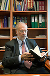 Dr Jean-Pierre Droz, Oncology unit, Centre Leon Berard, Lyon, France. The doctor in his office surrounded by books. Consulting his agenda or reading materials