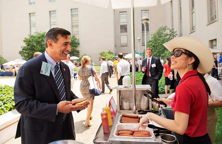 UNITED STATES - JULY 17: Rep. Darrell Issa, R-Calif., talks with Thao Grimes during the American Meat Institute's annual Hot Dog Lunch in the Rayburn courtyard. (Photo By Tom Williams/CQ Roll Call)