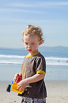 Three year old blonde boy holds toy truck standing on the beach and daydreams