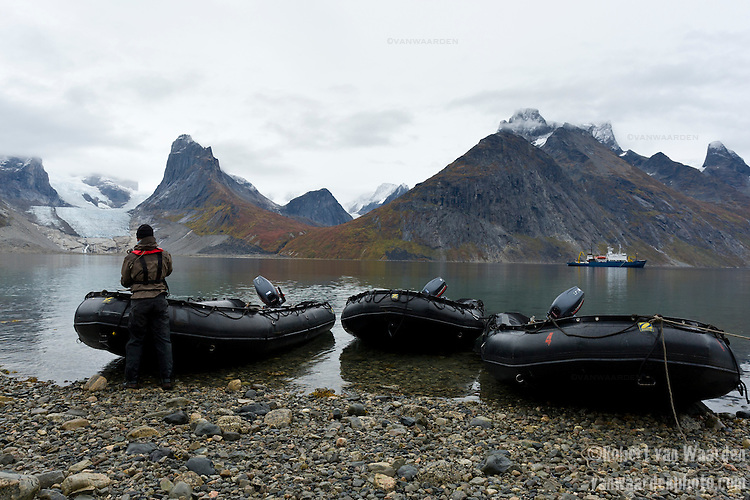 A man ties up the zodiacs during an expedition in Tasermiut Fjord, Greenland. In the background, glaciers and the expedition ship, Akademik Shokakskiy.