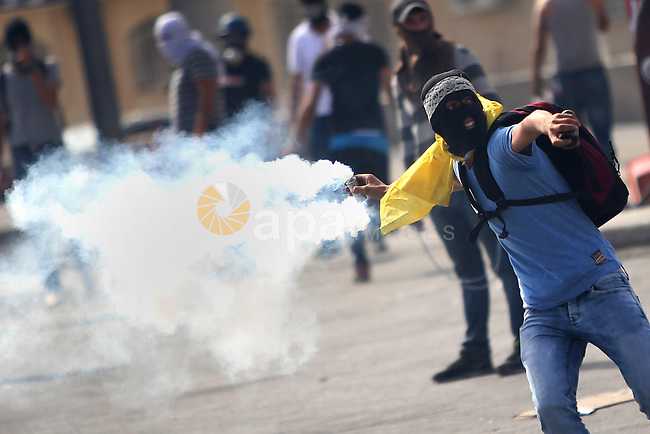 A Palestinian protester throws back a tear gas canister during clashes with Israeli security forces near the Jewish settlement of Bet El, near the West Bank city of Ramallah, on October 13, 2015. A wave of stabbings that hit Israel, Jerusalem and the West Bank this month along with violent protests in annexed east Jerusalem and the occupied West Bank, has led to warnings that a full-scale Palestinian uprising, or third intifada, could erupt. The unrest has also spread to the Gaza Strip, with clashes along the border in recent days leaving nine Palestinians dead from Israeli fire. Photo by Shadi Hatem