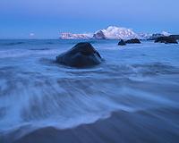 Waves flow across Myrland beach in December twilight, Flakstadøy, Lofoten Islands, Norway