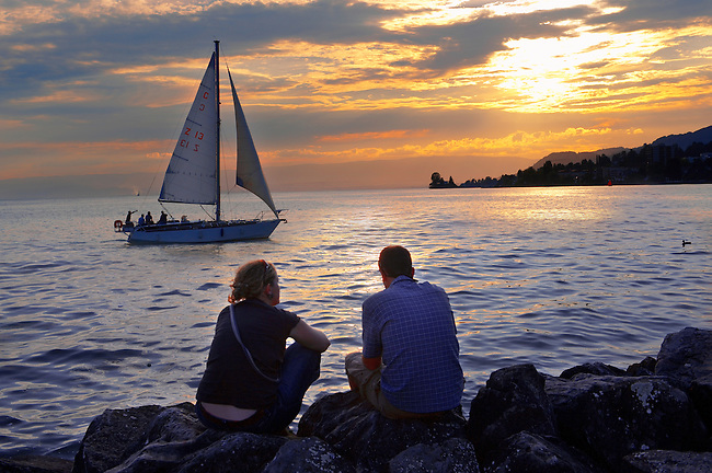 Youg couple watching a sailing boat at sunset on Lac Leman (lake Geneva) - Montraux Switzerland