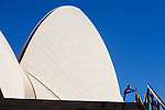 A runner stretches beneath the sail-like roofs of the Sydney Opera House. Sydney, New South Wales, AUSTRALIA.