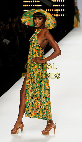 NAOMI CAMPBELL .At the Issa Show, London Fashion Week Day 3, Somerset House, London, England, UK,.September 20th 2009..full length modeling catwalk runway green and yellow print sarong cover up beach wear swimwear hat matching hands on hips halterneck brown sandals heels .CAP/CAN.©Can Nguyen/Capital Pictures.