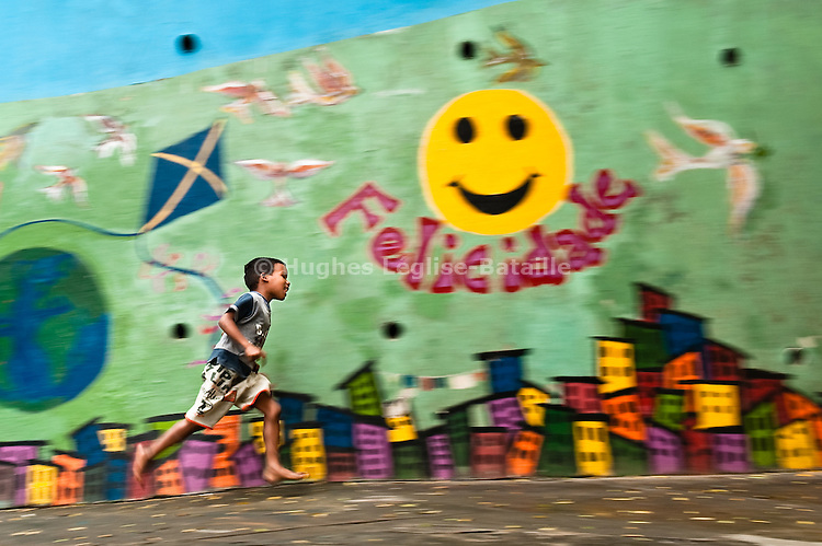 "A kid is running past a mural entitled ""Felicidade"" (happiness) in the ICP center in Gamboa, in Rio de Janeiro, Brazil."