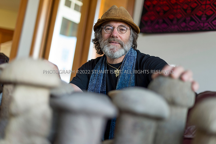 3/22/2013--Shelton, WA, USA..Paul Stamets poses with ancient Mayan mushroom stones he has collected in keeps in his home on his mushroom farm in Shelton, WASH., south of Seattle. Here he is also wearing his mushroom hat, made from Amadou, Fomes fomentarius...Paul Stamets, 57, is an American mycologist, author, and advocate of bioremediation and medicinal mushrooms and owner of Fungi Perfecti, a family run business that specializes in making gourmet and medicinal mushrooms. ..©2013 Stuart Isett. All rights reserved.