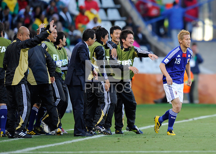 Keisuke Honda of Japan runs back onto the field after celebrating his goal with team-mates