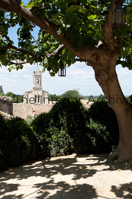 The bell tower of the village church is glimpsed beyond the tree at the end of the terrace