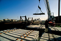 Workers off-load concrete rail ties from a flat-bed rail car using a crane.