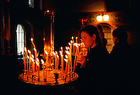 Woman worshipper holding a lighted candle in a church in Zagorsk, Russia