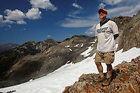 Backpacker standing on rocky outcrop overlooking glacier, Bailey Range Traverse, Olympic Mountains, Washington