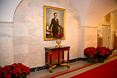 "The 2017 White House Christmas decorations, with the theme ""Time-Honored Traditions,"" which were personally selected by first lady Melania Trump, are previewed for the press in Washington, DC on Monday, November 27, 2017.  Poinsettia plants are under the official portrait of former first lady Hillary Rodham Clinton in the Ground Floor Corridor.<br /> Credit: Ron Sachs / CNP"
