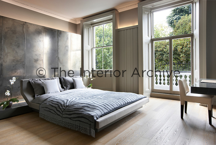 A contemporary bedroom has been created in a Victorian-era apartment block, which retains the original windows and cornicing. Light reflects off a large metallic cabinet installed behind a king size bed. A writing desk and chair stand in one corner.