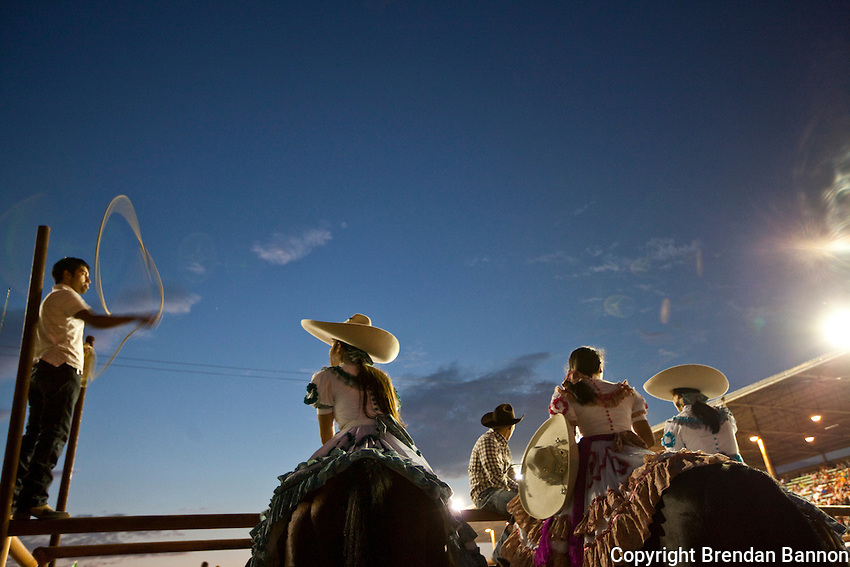 Members of Escaramuza Las Gazelas, a group of women side saddle horse riders at the Kern County Fair, watch the rodeo performers do their thing.