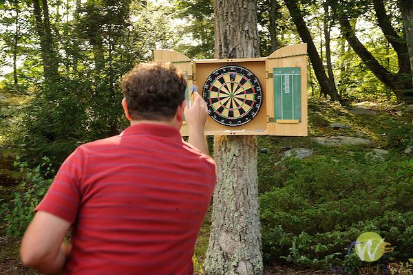 Outdoor dart board mounted on tree.