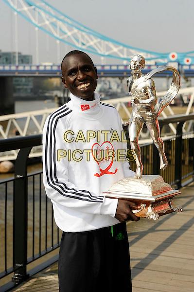 EMMANUEL MUTAI  .London Marathon Winners 2011 Photocall, Guoman Hotel, Tower Bridge, London, England..April 18th, 2011.athlete half length award trophy white jacket top winner smiling  .CAP/CJ.©Chris Joseph/Capital Pictures.