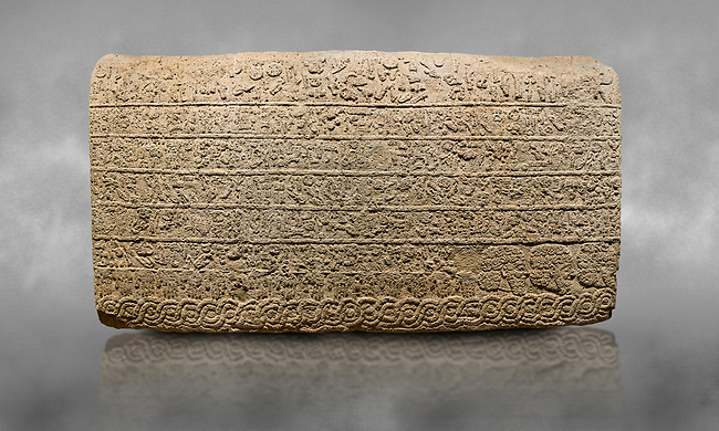 Hittite sculpted Orthostats panel from the  Long Wall.  Limestone, Kargarmis, Gaziantep, 900 - 700 BC,  Hieroglyph. Anatolian Civilisations Museum, Ankara, Turkey.<br /> <br /> In the epigraph with hieroglyph, he narrates that the gods were provoked against him, the account of the cities conquered and the spoils of war; that he allocated a share for the gods, and that he instigated the mighty king Tarhunza and the other gods. In the other lines, he demands that people should present offerings to statues but should evil-intentioned people be among them, such person individuals be punished by the gods.  <br /> <br /> On a grey art background.