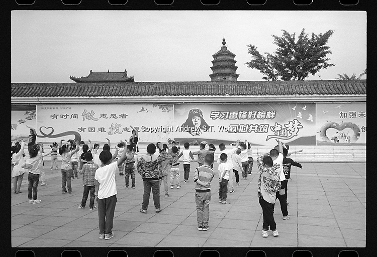Lu'an, Anhui province, China - Kindergarten students take part in morning exercise in front of propaganda billboards at the Northern Pagoda Park, May 2017.