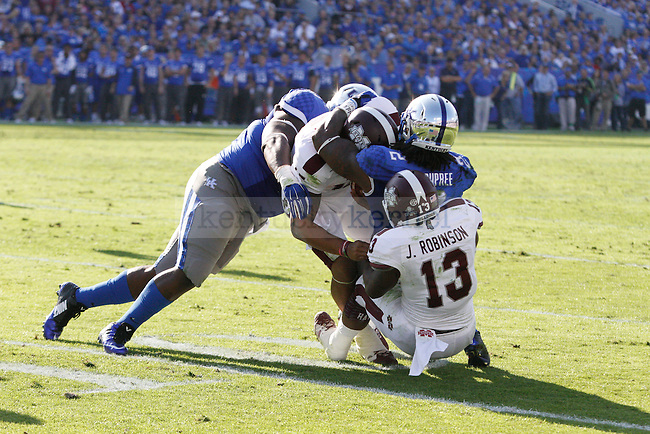 Mississippi State quarterback Dak Prescott (15) gets tackled by defensive end Tymere Dubose (98) of the Kentucky Wildcats during the first half of the game against the Mississippi State Bulldogs at Commonwealth Stadium on Saturday, October 25, 2014 in Lexington, Ky. Mississippi State defeated Kentucky 45-31. Photo by Hunter Mitchell | Staff