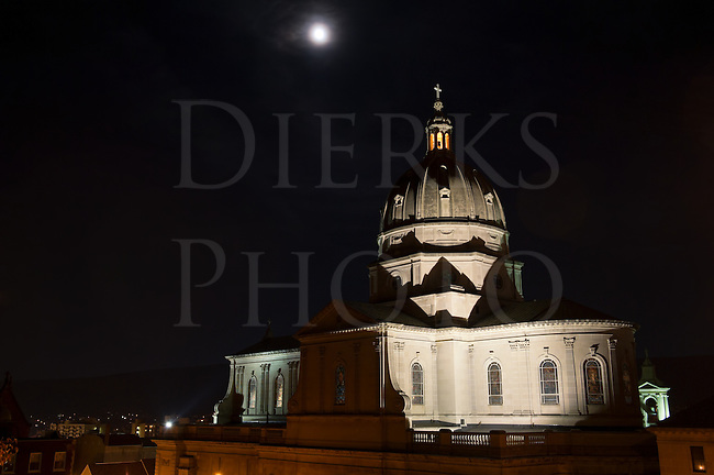 Cathedral church dome under full moon, photographed at night with rotunda and cross lit, Altoona, PA, USA.