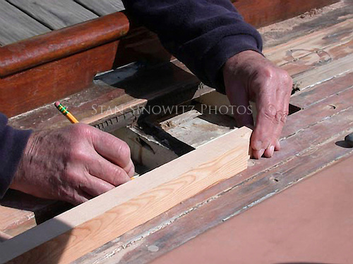 The experienced hands of a shipwright.  Marking a replacement plank for the deck.