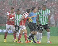 BOGOTÁ -COLOMBIA, 07-05-2014. Jugadores de Santa Fe y Nacional discuten con el árbitro, Luis Sanchez (de azul) tras suspender por lluvia el encuentro de ida entre Independiente Santa Fe y Atlético Nacional por la semifinales de la Liga Postobón I 2014 jugado en el estadio Nemesio Camacho El Campín de la ciudad de Bogotá./ Players of Santa Fe and Nacional  discussed with Luis Sanchez (blue shirt), referee, after he suspended due to rain the first leg match between Independiente Santa Fe and Atletico Nacional for the semifinals of the Postobon League I 2014 played at Nemesio Camacho El Campin stadium in Bogotá city. Photo: VizzorImage/ Gabriel Aponte / Staff