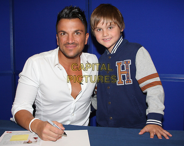 Peter Andre at a signing in WH Smith, Milton Keynes to launch his new range of children's books - published by Ladybird. Titles include 'A New Day at School' and 'The Happy Birthday Party', Milton Keynes, England..September 5th 2011.half length white shirt table sitting kid child blue jacket.CAP/JIL.©Jill Mayhew/Capital Pictures